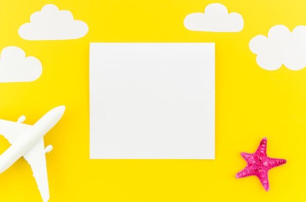 Petit avion jouet avec nuages et papier vierge Photo gratuit