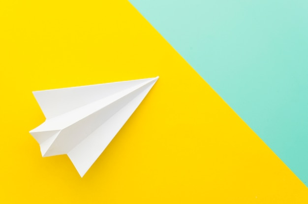 Petit avion en papier sur la table Photo gratuit
