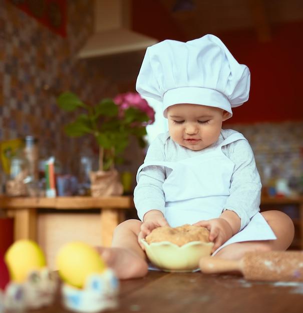 Le petit bébé assis sur la table et jouant avec de la pâte Photo gratuit