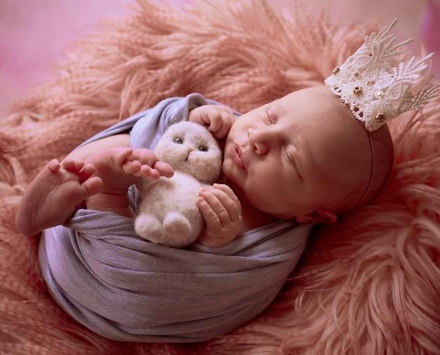Le petit bébé avec une couronne se trouve dans le panier Photo gratuit