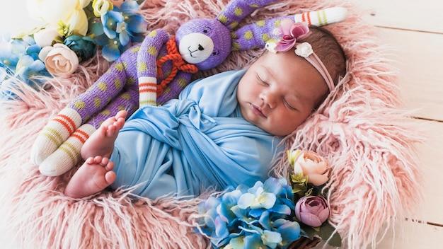 Petit bébé dort avec un ami de jouet Photo gratuit