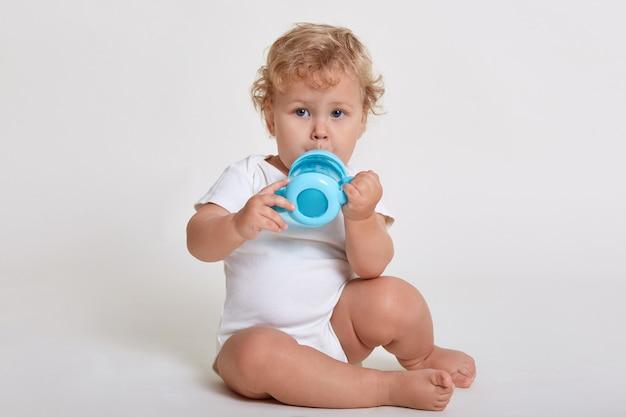 Petit Bébé Enfant Buvant De La Bouteille Bleue Photo Premium