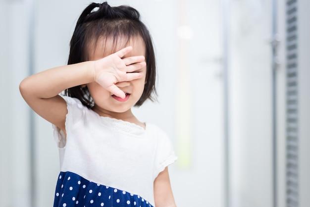 Petit bébé enfant tenant une poupée craignant de sortir par la porte Photo Premium