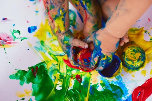 Le Petit Bébé Est Assis Près De Différentes Peintures Photo gratuit