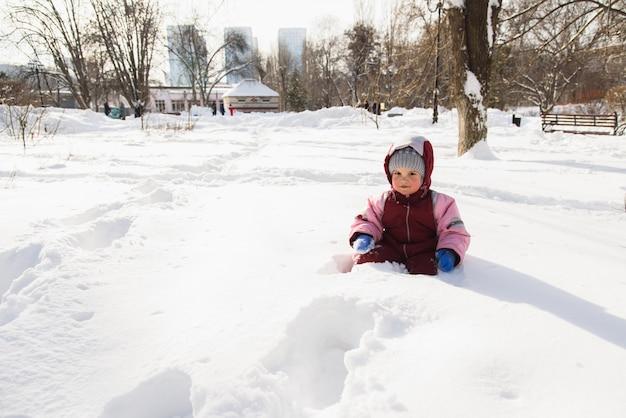 Petit bébé est tombé dans la neige et est assis Photo Premium