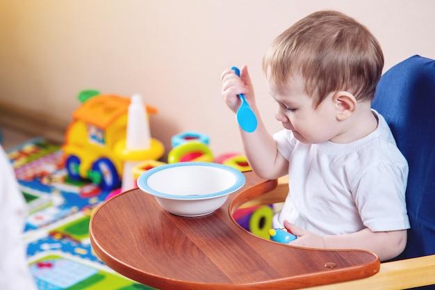 Petit bébé garçon apprend à manger à une table en étudiant une assiette et une cuillère dans la cuisine Photo Premium