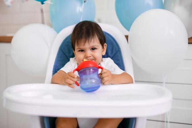 Petit Bébé Garçon Assis Dans Une Chaise Haute à La Maison Sur Une Cuisine Blanche Et De L'eau Potable à Partir D'une Tasse Sur Fond Avec Des Ballons. Photo Premium