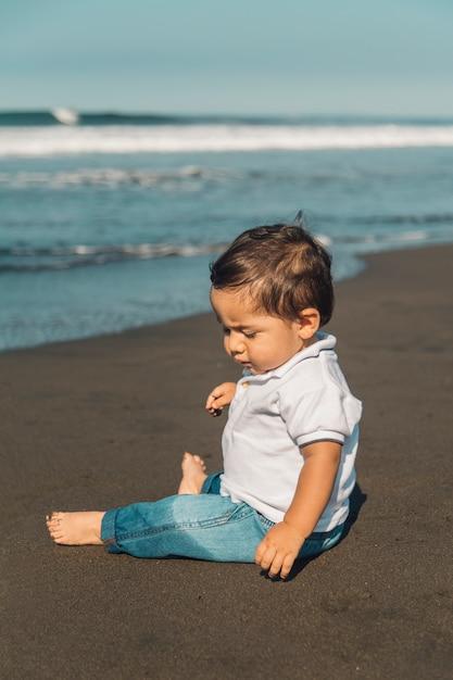 Petit bébé garçon assis sur le sable de la plage Photo gratuit