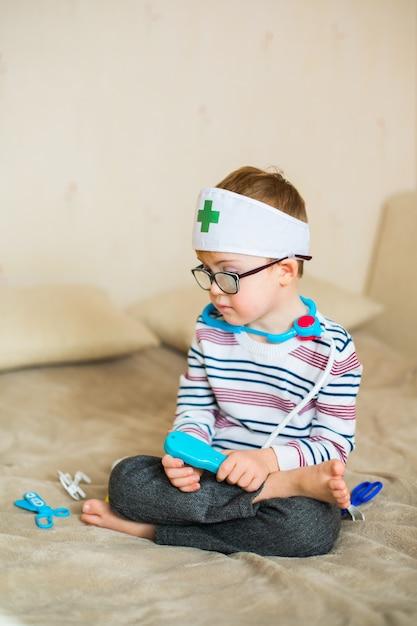 Petit Bébé Garçon Atteint Du Syndrome De Down Avec De Grandes Lunettes Bleues Jouant Avec Des Jouets De Médecin Photo Premium