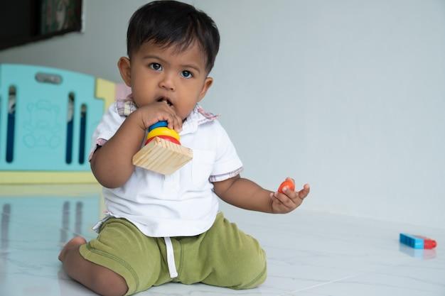 Petit bébé garçon joue un jouet en bois dans la chambre Photo Premium