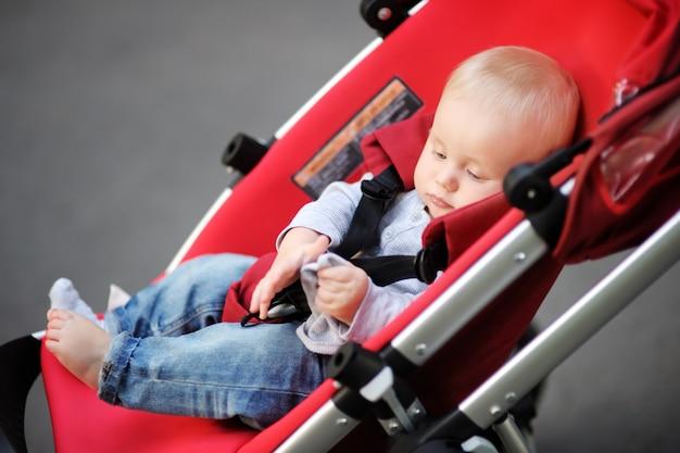 Petit bébé garçon en poussette jouant avec sa chaussette Photo Premium