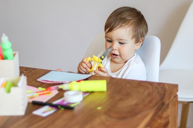 Petit bébé garçon tenant des ciseaux dans ses mains et faire une carte de voeux en papier à la main Photo Premium