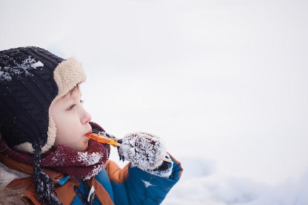 Petit bébé jouant et mangeant du coq sucré en journée d'hiver. les enfants jouent dans la forêt enneigée. Photo Premium