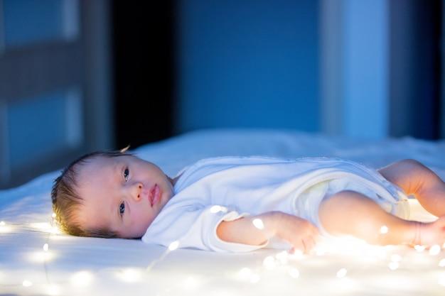 Petit bébé sur un lit blanc Photo Premium