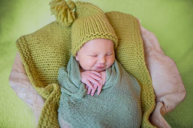 Petit bébé nouveau-né en vêtements tricotés dort sur l'oreiller Photo gratuit