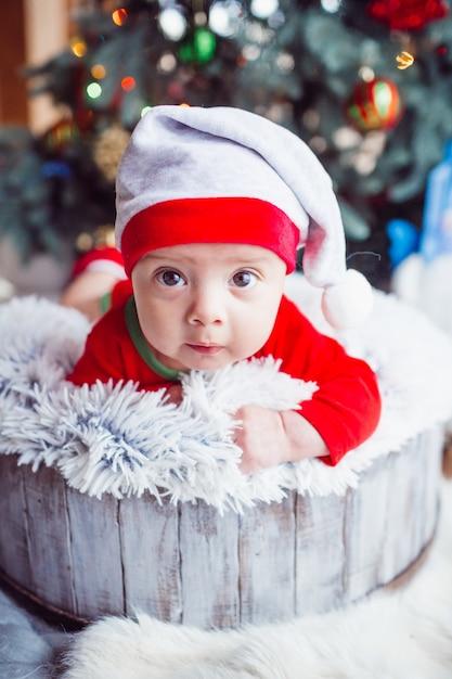 Le petit bébé se trouve près de l'arbre de noël Photo Premium