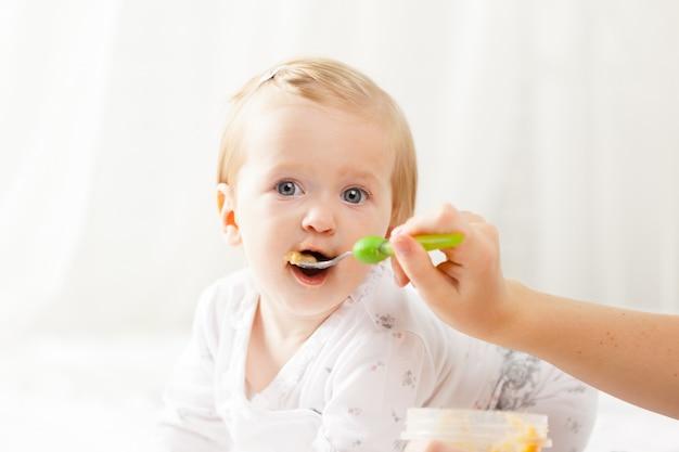 Petit bébé tétant avec une cuillère Photo Premium
