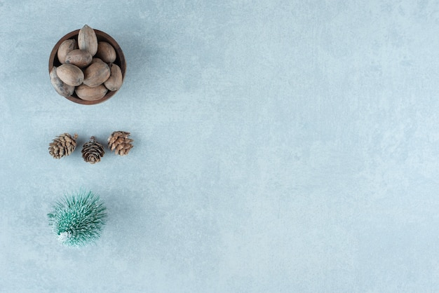 Petit Bol D'amandes, Pommes De Pin Et Figurine D'arbre Sur Marbre. Photo gratuit