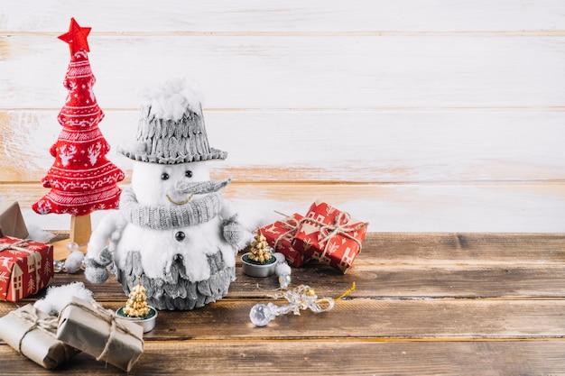 Petit bonhomme de neige avec des boîtes-cadeaux sur la table Photo gratuit