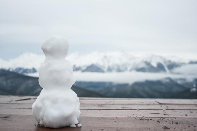 Un petit bonhomme de neige est debout sur une table, à l'arrière-plan, les pics de la montagne Photo Premium