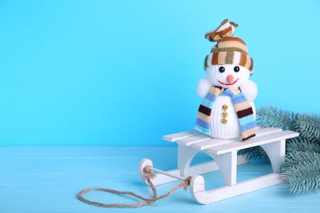 Petit bonhomme de neige avec traîneau blanc sur fond bleu Photo Premium