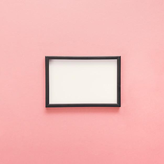 Petit cadre vierge sur table rose Photo gratuit