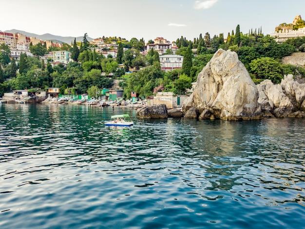 Petit catamaran touristique passant par la côte rocheuse sur la mer Photo Premium