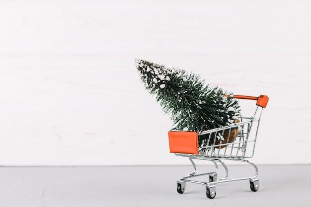 Petit chariot d'épicerie avec sapin Photo gratuit