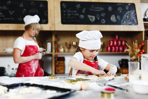 Petit chef. charmante fille s'amuse à faire des biscuits d'une pâte dans une cuisine confortable Photo gratuit