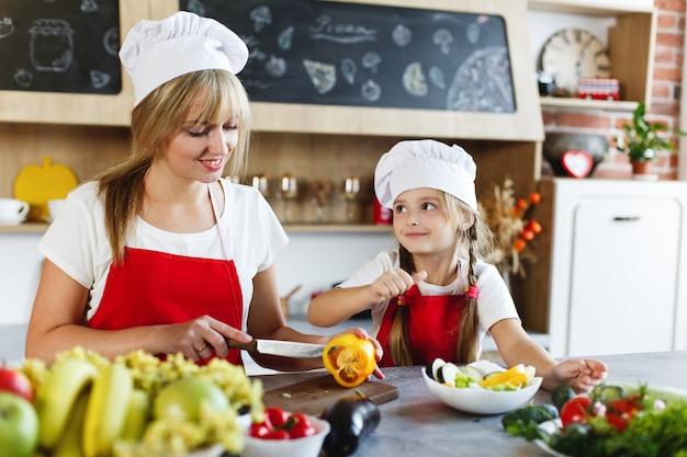 Petit chef. maman et sa charmante fille s'amusent à préparer des légumes dans une cuisine confortable Photo gratuit