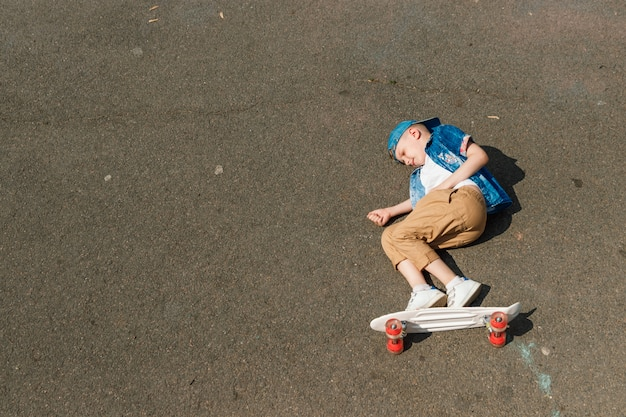 Un petit citadin et skateboard. un jeune mec chevauche une planche de skate parka Photo Premium