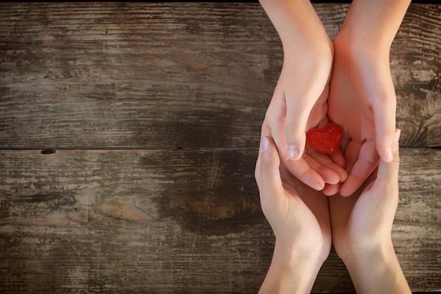 Petit coeur rouge se trouve entre les mains des hommes et des femmes, le concept de l'amour et de la romance. Photo Premium