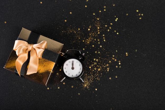 Petit coffret cadeau avec horloge sur tableau noir Photo gratuit