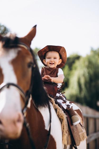 Petit cow-boy assis sur un cheval Photo gratuit