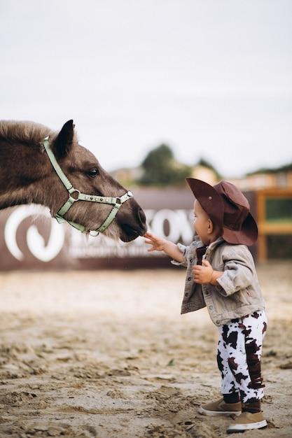 Petit cowboy au ranch Photo gratuit