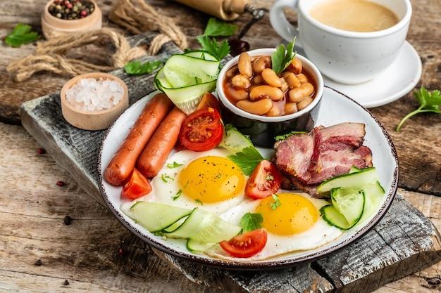 Petit-déjeuner Anglais Traditionnel Avec œufs Au Plat, Bacon, Haricots, Café Et Saucisse, Menu Du Restaurant, Régime, Recette De Livre De Cuisine. Photo Premium