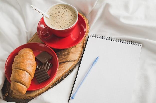 Petit déjeuner au lit et cahier vide pour la note. Photo Premium
