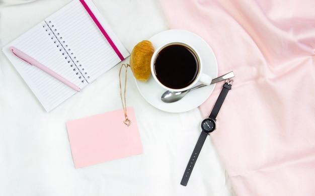 Petit déjeuner au lit. composition plate avec du café, des croissants et un cahier pour écrire. cadre de vie. vue de dessus sur les feuilles Photo Premium