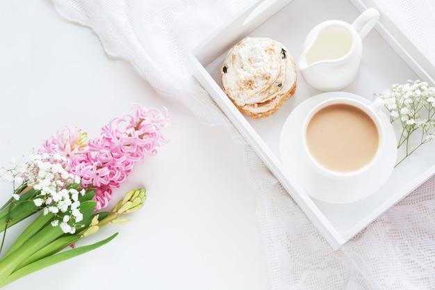 Petit déjeuner au printemps avec une tasse de café noir avec du lait et des pâtisseries aux couleurs pastel Photo Premium