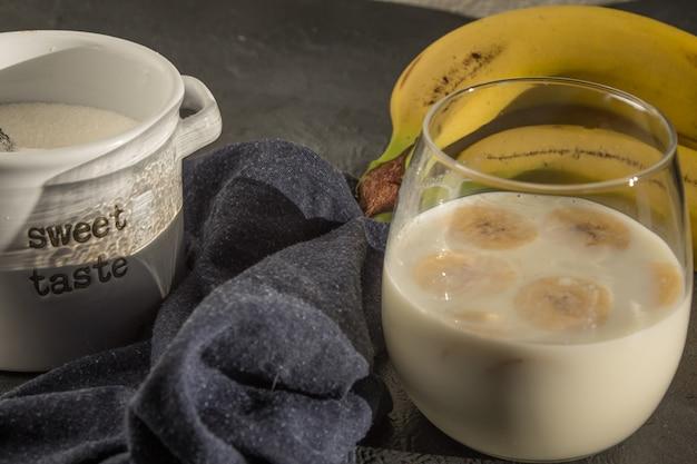 Petit déjeuner à la banane avec du lait avec du sucre, du pain grillé et des biscuits Photo Premium