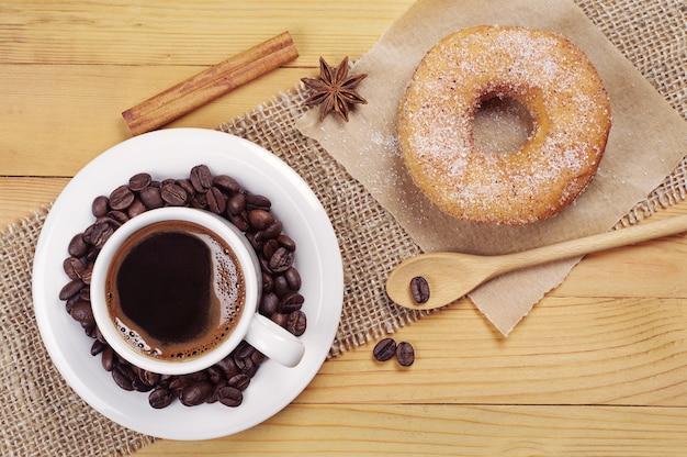 Petit-déjeuner Avec Beignet Sucré Et Tasse De Café Chaud Sur Table En Bois Photo Premium