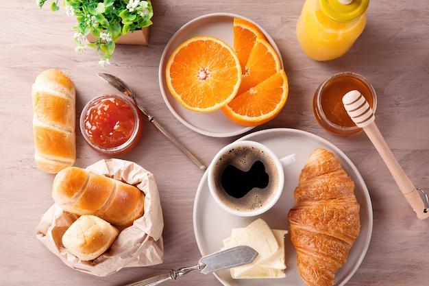 Petit déjeuner avec café, jus d'orange et croissant. vue de dessus Photo Premium