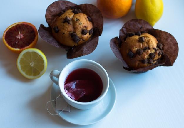 Petit déjeuner avec café et thé avec différentes pâtisseries et fruits sur une table en bois blanche Photo Premium