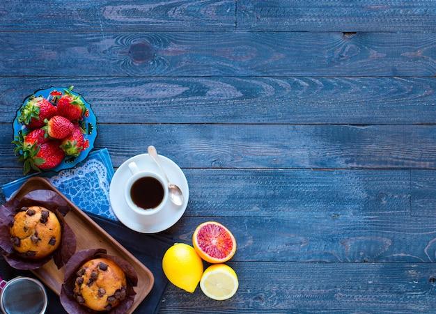 Petit déjeuner avec café et thé avec différentes pâtisseries et fruits sur une table en bois Photo Premium