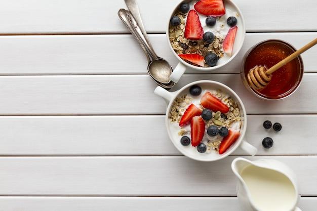 Petit déjeuner coloré savoureux avec de la farine d'avoine, du yaourt, de la fraise, du myrtille, du miel et du lait sur fond de bois blanc avec un espace de copie. vue de dessus. Photo gratuit