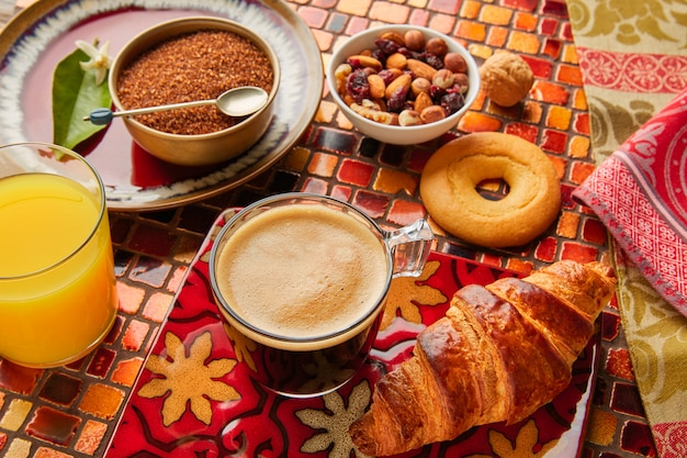 Petit-déjeuner continental croissant café jus d'orange Photo Premium