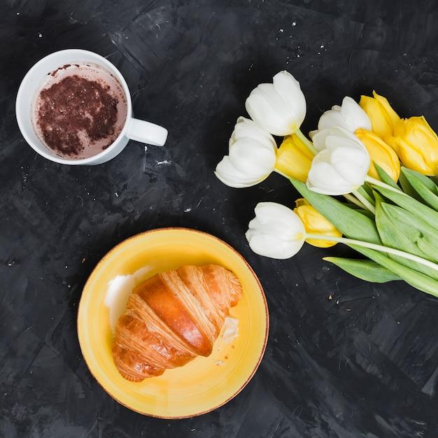 Petit déjeuner avec croissant et fleurs Photo gratuit