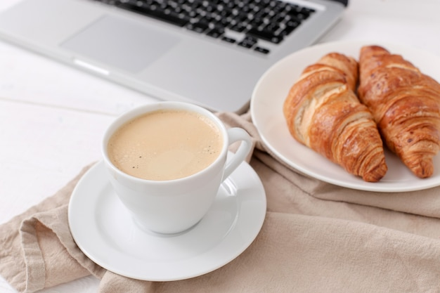 Petit-déjeuner Avec Croissants Et Café Près D'un Ordinateur Portable Photo gratuit