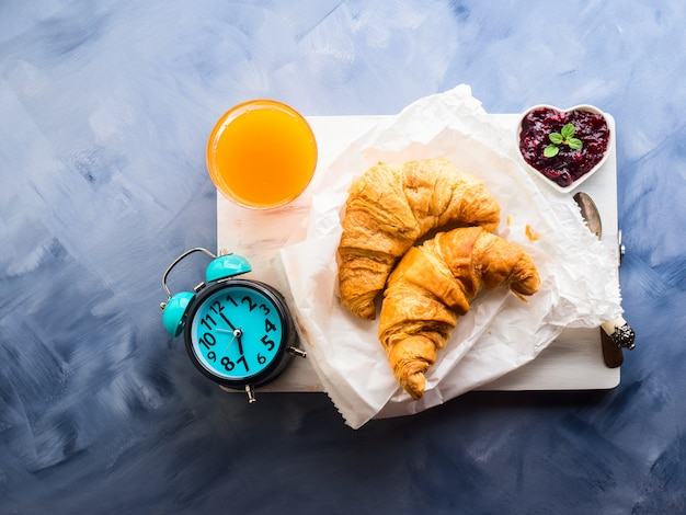 Petit déjeuner avec des croissants servis sur une planche de bois Photo Premium