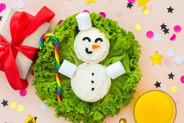 Petit-déjeuner Drôle De Noël, Sandwichs, Bonhomme De Neige, Bonbons Arc-en-ciel, Guimauves. Photo Premium